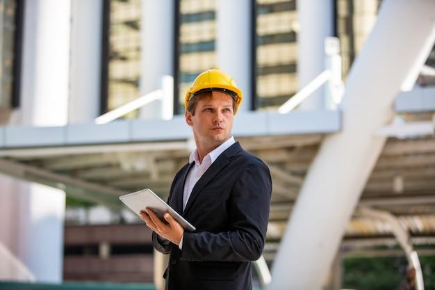 Biznesmen lub majster z kaskiem patrząc na plan przeciwko budynku