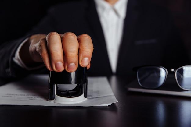 Biznesmen (lub notariusz) siedzi przy biurku w biurze i stempluje dokument