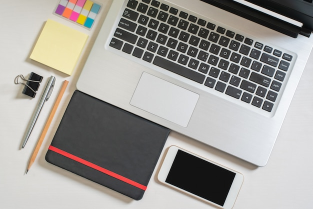 Biznesmen lub oficer, laptop, czarny notatnik, mini kolorowa notatka papierowa, telefon komórkowy, długopis, ołówek