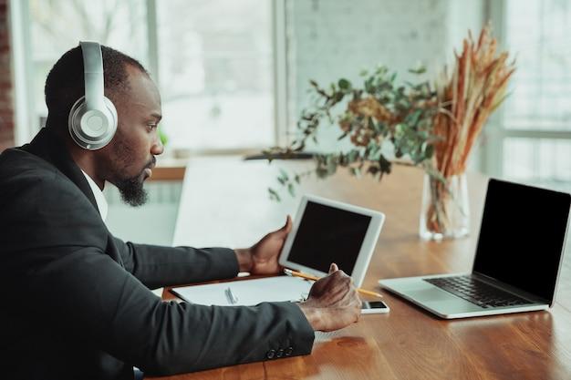 Biznesmen lub student pracujący w domu jest odizolowany lub poddaje się kwarantannie z powodu koronawirusa. afro-człowiek za pomocą laptopa, tabletu i słuchawek. konferencja online, lekcja, zdalne biuro.