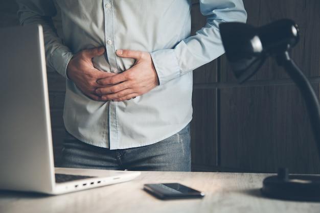 Biznesmen ma ból żołądka w pokoju roboczym