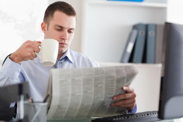 Biznesmen ma kawę podczas gdy czytający gazetę