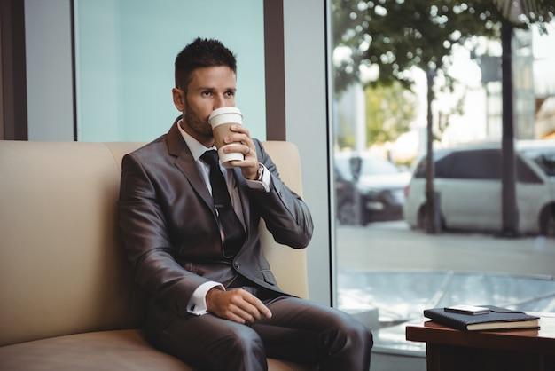 Biznesmen ma kawę podczas gdy siedzący na kanapie