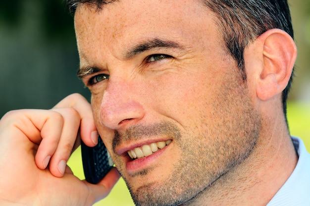 Biznesmen ma komunikację ze swoim telefonem komórkowym