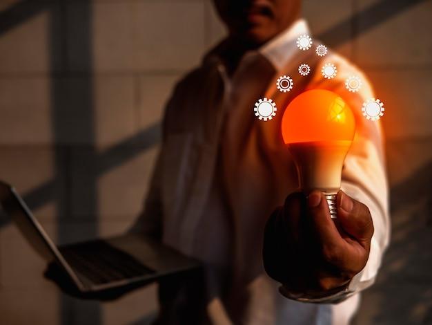 Biznesmen ma koncepcję rozwiązania zilustrowaną świecącą bańką szklaną w ręku