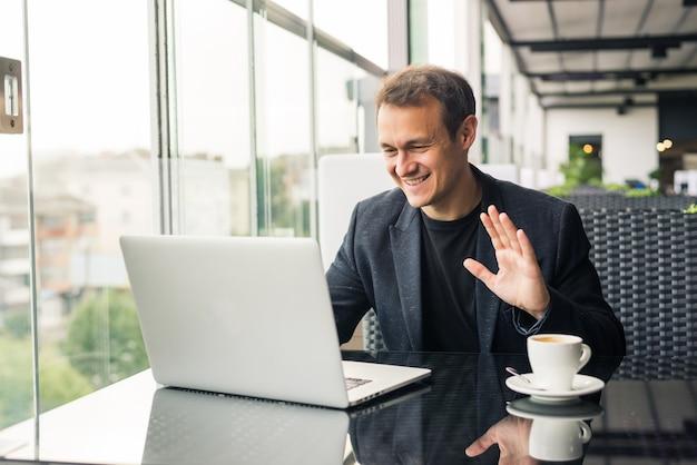 Biznesmen ma spotkanie biznesowe za pośrednictwem połączenia wideo w kawiarni