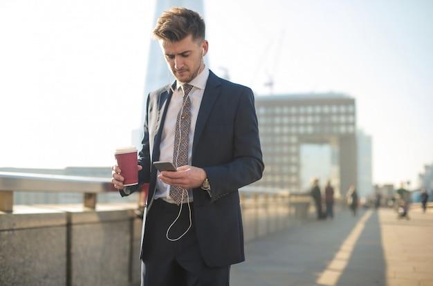 Biznesmen ma wezwanie podczas gdy chodzący w ulicie