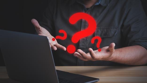 Biznesmen ma wiele pytań, zastanawiając się, co dalej robić przed swoim laptopem.