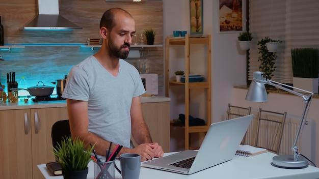 Biznesmen macha podczas wideokonferencji podczas pracy w domu w nocy. pracownik korzystający z nowoczesnych technologii o północy wykonujący nadgodziny w pracy, biznesie, karierze, sieci, stylu życia, bezprzewodowo.