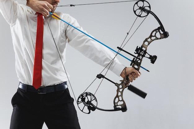 Biznesmen, mające na celu z łukiem i strzałami, na białym tle na szarym tle studio. biznes, cel, wyzwanie, konkurencja, koncepcja osiągnięcia