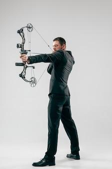 Biznesmen, mające na celu z łukiem i strzałami, na białym tle na szarym tle studio.