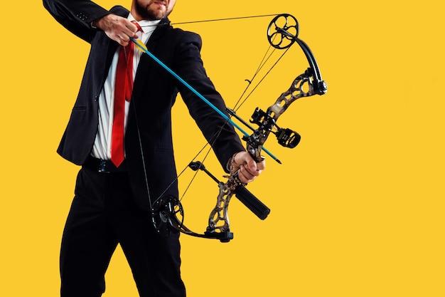 Biznesmen mające na celu z łukiem i strzałami, na białym tle na żółtej ścianie studio