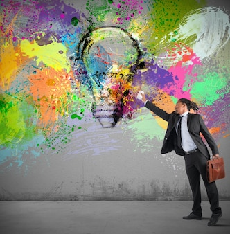Biznesmen maluje na ścianie kolorowy pomysł sprayem