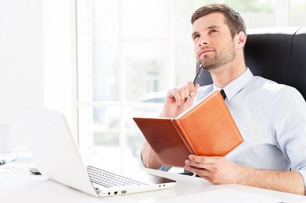Biznesmen marzy. rozważny młody człowiek w koszuli i krawacie, trzymając notatnik i odwracając wzrok, siedząc w swoim miejscu pracy