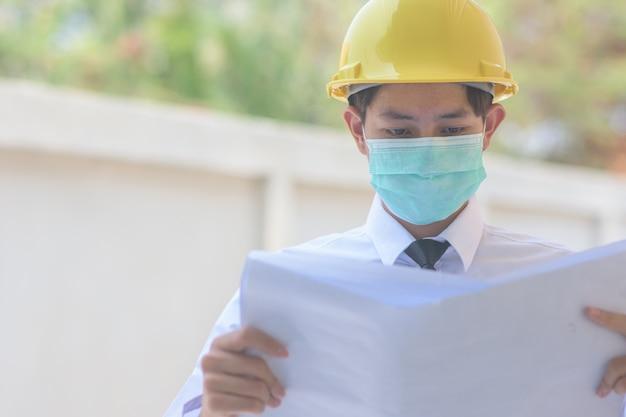 Biznesmen maska chirurgiczna chroni pm2.5 i trzyma plan na budowie