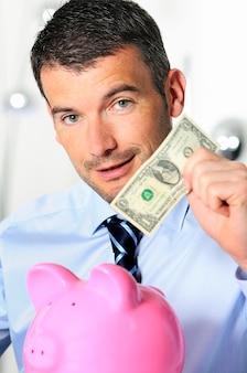 Biznesmen matowanie monety w różowej świni w kształcie świnki