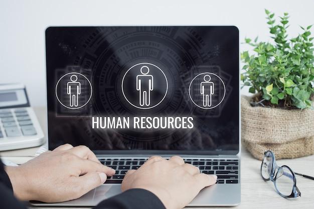 Biznesmen menedżer przy użyciu komputera z ikonami znak działu zasobów ludzkich (dział hr) na laptopie. biznes jako przestrzeganie prawa pracy, standardy zatrudnienia, administracja świadczeniami pracowniczymi