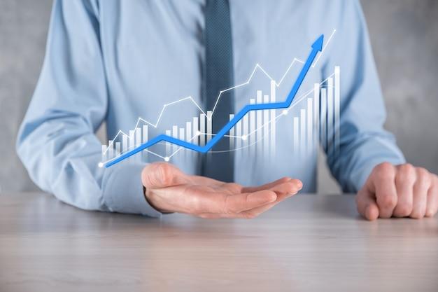 Biznesmen mężczyzna trzyma wykres z dodatnim wzrostem zysków. planować wzrost wykresów i wzrost pozytywnych wskaźników wykresu w swojej firmie. bardziej zyskowny i rosnący.