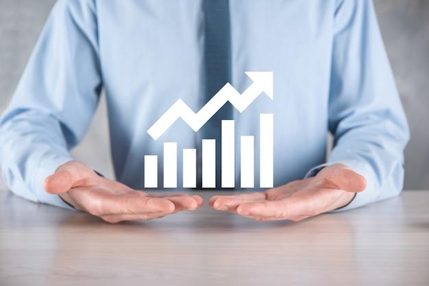 Biznesmen mężczyzna trzyma wykres z dodatnim wzrostem zysków. planować wzrost wykresu i wzrost pozytywnych wskaźników wykresu w swojej firmie. bardziej rentowny i rosnący.