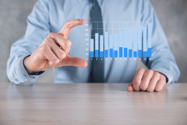 Biznesmen mężczyzna trzyma wykres z dodatnim wzrostem zysków. planować wzrost wykresu i wzrost pozytywnych wskaźników wykresu w swojej firmie. bardziej zyskowny i rosnący.