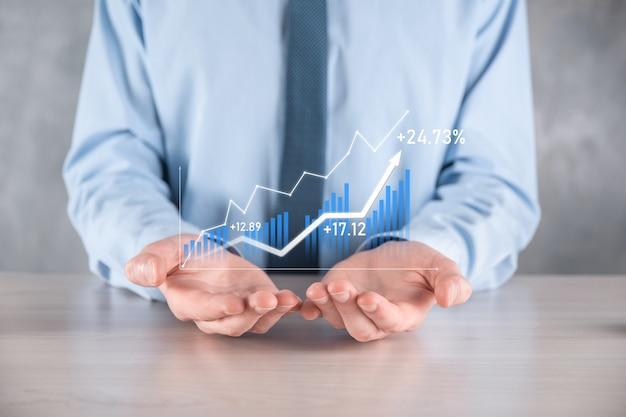 Biznesmen mężczyzna trzyma wykres z dodatnim wzrostem zysków.