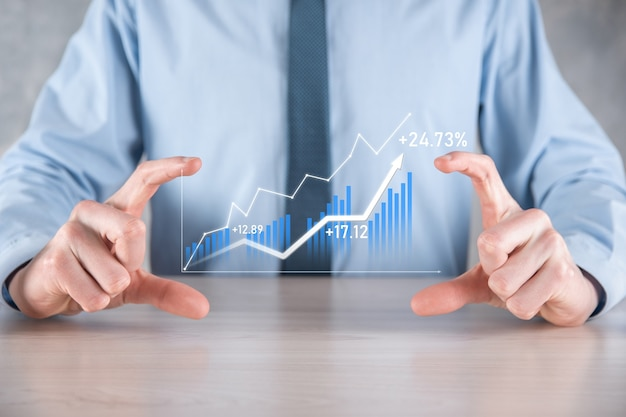 Biznesmen mężczyzna trzyma wykres z dodatnim wzrostem zysków