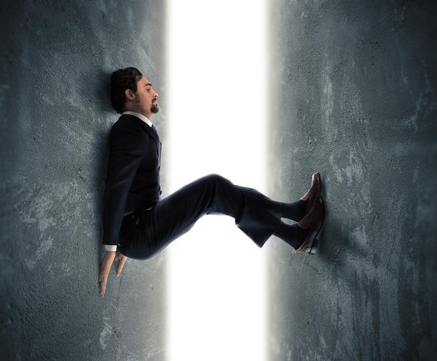 Biznesmen mężczyzna uwięziony między dwiema ścianami próbuje pchać