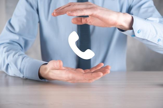 Biznesmen mężczyzna w koszuli z krawatem na szarej ścianie przytrzymaj ikonę telefonu. zadzwoń teraz centrum wsparcia komunikacji biznesowej koncepcja technologii obsługi klienta.