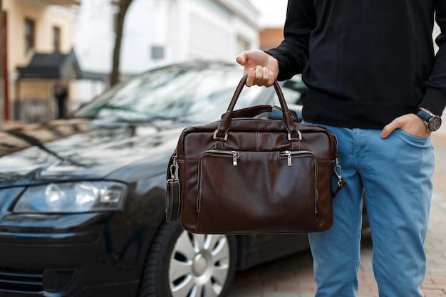 Biznesmen mężczyzna ze skórzaną torbą w pobliżu czarnego samochodu