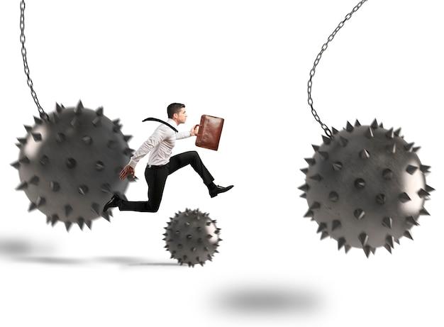 Biznesmen między ostrymi, kolczastymi piłkami, które przeszkadzają