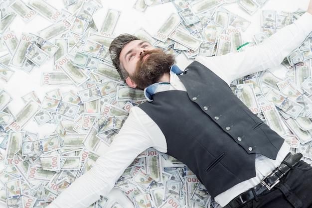 Biznesmen milioner brodaty mężczyzna z wieloma banknotami biznesmen leżący w banknotach