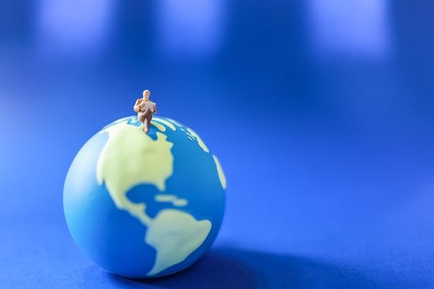 Biznesmen miniaturowa postać ludzi czytających bookon mini światowa piłka