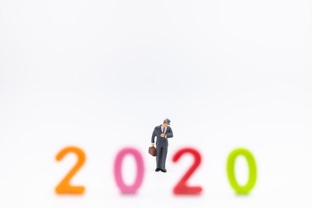 Biznesmen miniaturowa postać ludzi z walizką stojący i patrząc na zegarek na rękę