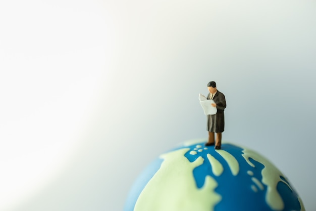 Biznesmen miniaturowe postacie ludzi stojących i czytających gazetę na mini kuli świata.