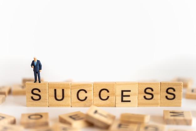 Biznesmen miniaturowe postacie ludzi stojących z kciukiem do góry na drewnianym bloku literowym z sformułowaniem sukces.