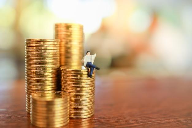 Biznesmen miniaturowe rysunek ludzi siedzi i czyta gazetę na stosie monet