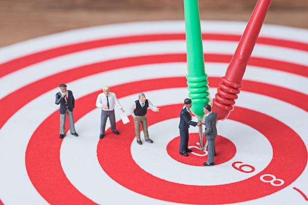 Biznesmen miniaturowe zespołu umowy na czerwone i zielone rzutki w centrum tarczy
