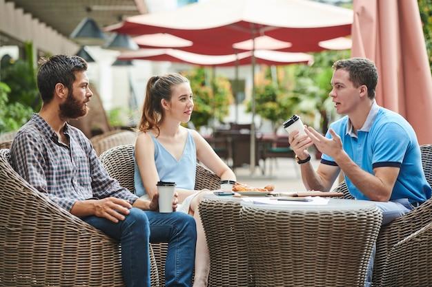 Biznesmen mówi pomysły współpracownikowi w kawiarni
