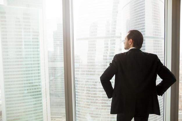 Biznesmen myśleć o przyszłościowym pobliskim okno