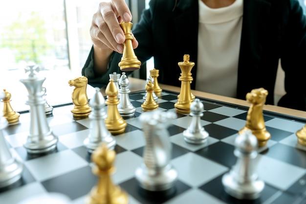 Biznesmen myślenia i trzymać króla szachy na rękę