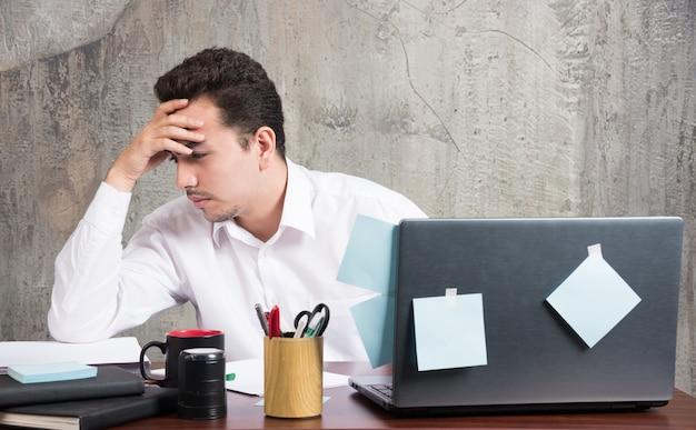Biznesmen myśli o czymś przy biurku.