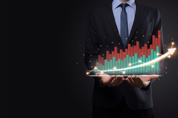 Biznesmen na czarnym tle naciska, naciska palcem na dodatnią strzałkę wzrostu. wykresy wskaźników. koncepcja rozwoju biznesu i finansów.