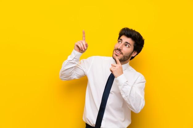 Biznesmen na odosobnionym kolorze żółtym wskazuje z palcem wskazującym świetnego pomysł