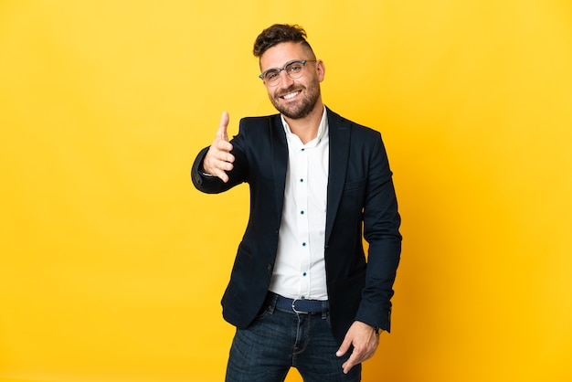 Biznesmen na pojedyncze żółte tło drżenie rąk za zamknięcie dobrą ofertę