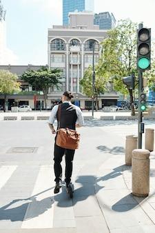 Biznesmen na skrzyżowaniu hulajnogi na zielonym świetle, widok z tyłu