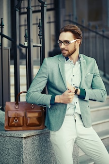 Biznesmen na sobie garnitur na ulicy z brązową torbę