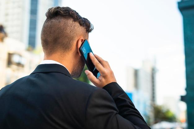 Biznesmen na zewnątrz rozmawia przez telefon z tyłu strzału
