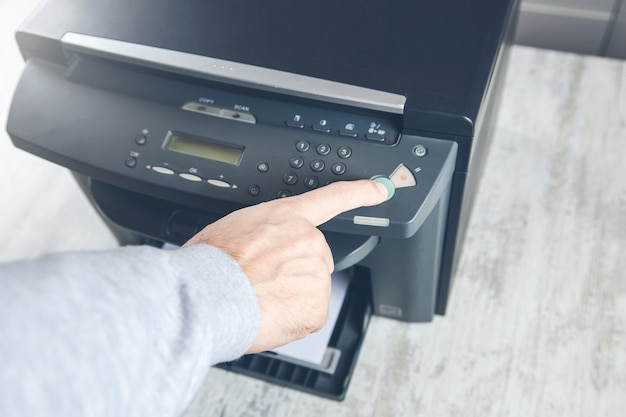Biznesmen naciskając przycisk na panelu za pomocą kserokopiarki