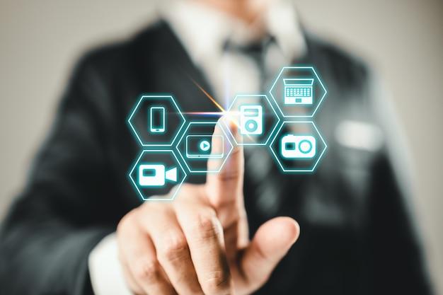 Biznesmen naciskając wirtualną ikonę multimediów typu przycisków