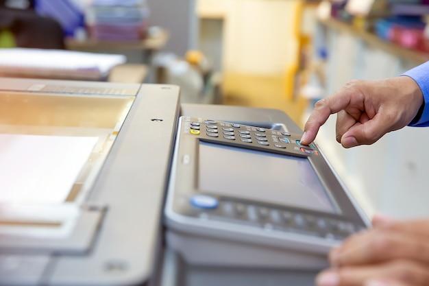Biznesmen naciśnij przycisk na panelu kserokopiarki.